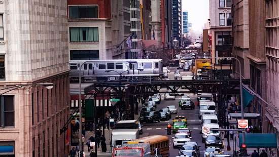 A city corridor with traffic congestion and a train overhead.