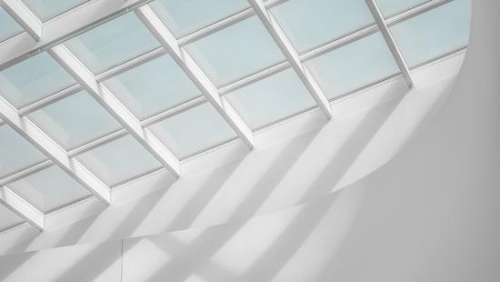 Light comes through mutiple square panes in a skylight.