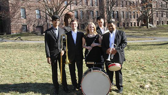five students with various instruments standing outside a building at Cornell