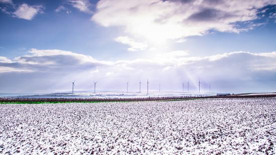 Distant wind turbines on a snowy flat landscape.