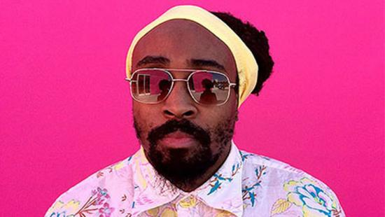 A bearded man wearing a knit cap and sunglasses against a pink background.