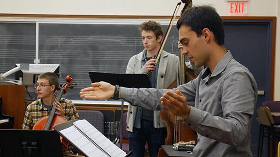 """Composer Patrick Braga conducts music for """"Eyes That Do Not See"""" during a rehearsal in Lincoln Hall with musicians Colin Barber '17 and Chris Worden '19."""