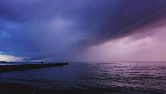 A storm cloud over the ocean in a blue and purple hue.