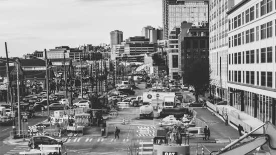 A crowded cityscape with vehicles, people, buildings, and restraunts.