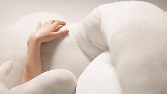 A picture of a hand reaching out of white stuffed fabric