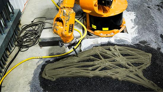 A robotic arm in action fabricating a designed pattern in concrete.