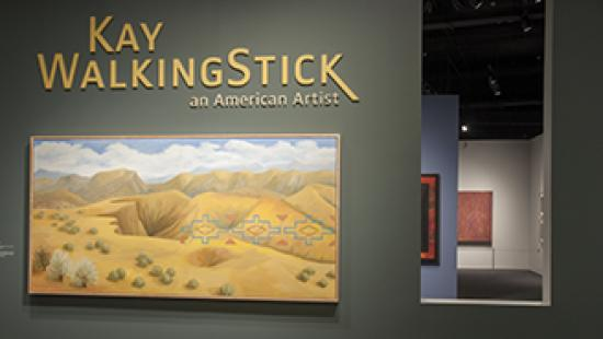 Entrance to WalkingStick exhibition with name and landscape painting