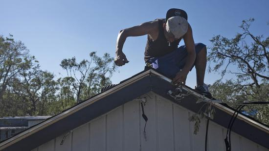 A person kneeling on a peaked roof, blue sky, trees.