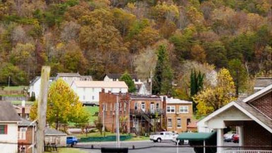 Low buildings, streets, and homes, a wooded mountainside.