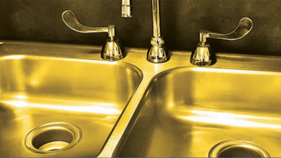 A gold-colored double sink with faucet handles and spigot.