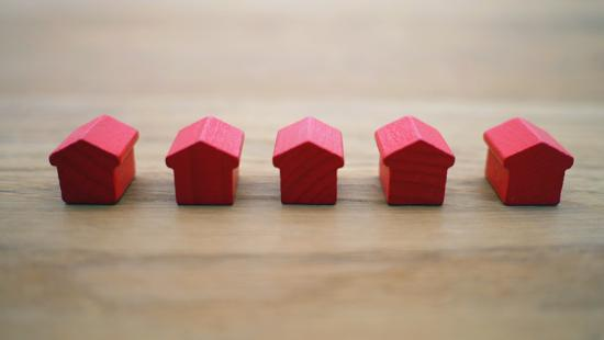 Five miniature, red house shapes in a row on a wood surface.