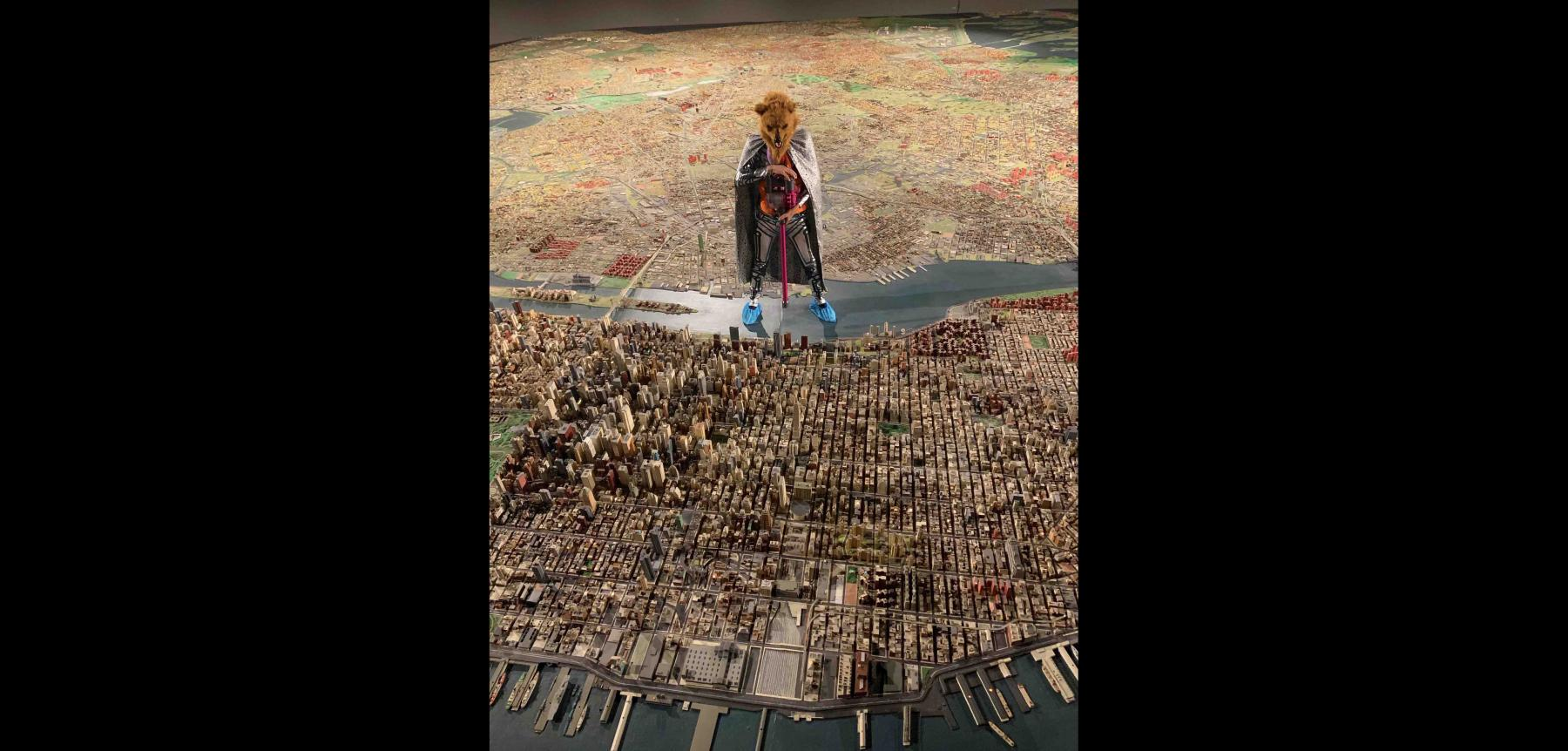 Figure wearing an animal mask and cape with blue slippers on feet, standing in a flat river on a large scale map depicting a land mass behind the figure and a city in front of it.