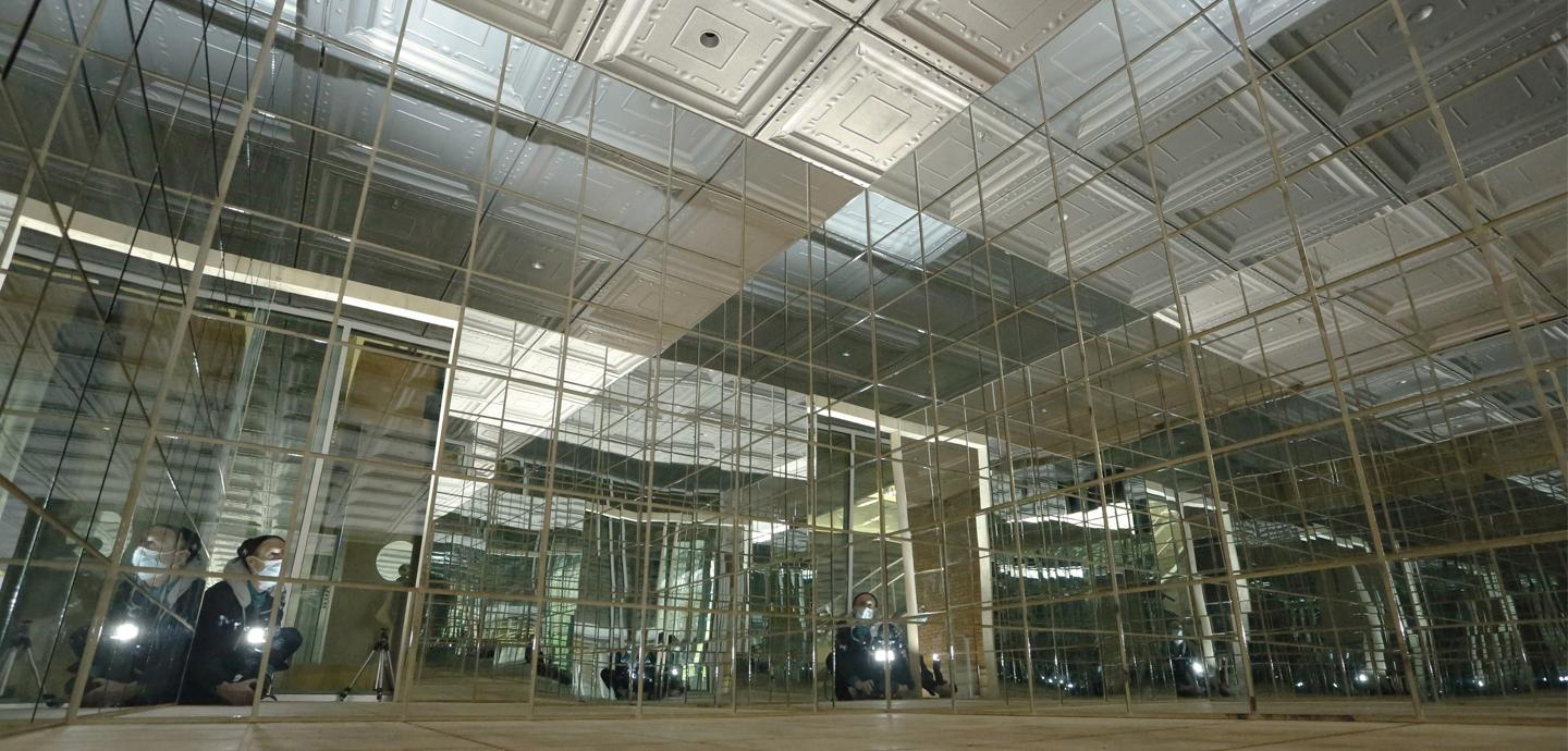A view of a cube structure from within covered in mirrors.