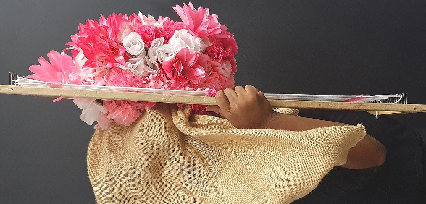 A hand holding up a woven structure consisting of burlap material and pink artificial flowers.