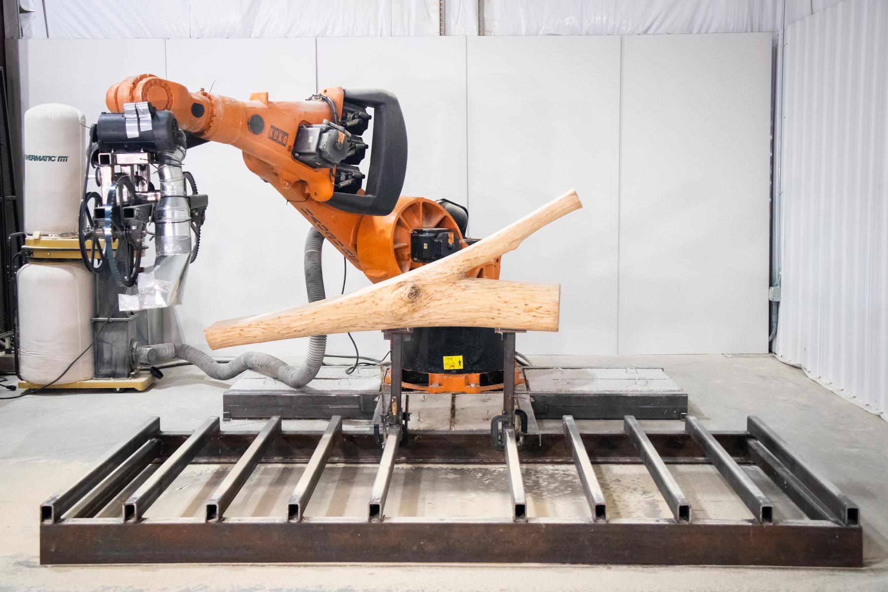robotic chainsaw arm preparing to cut a log