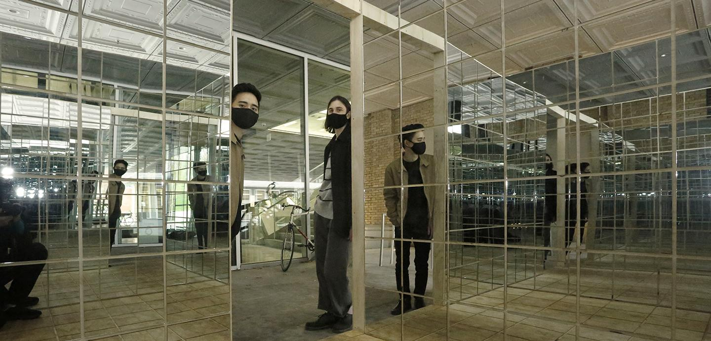 Two people with masks in the doorway of a mirrored box structure.