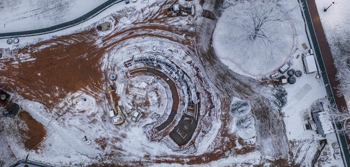 aerial view of construction and site work for a semi circle monument project with a thin layer of white snow on red clay ground