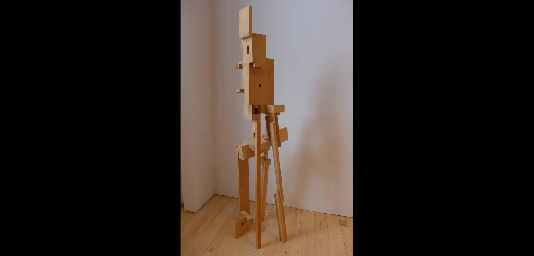 Abstract wooden sculpture piece with various sized rectangular pieces put together.