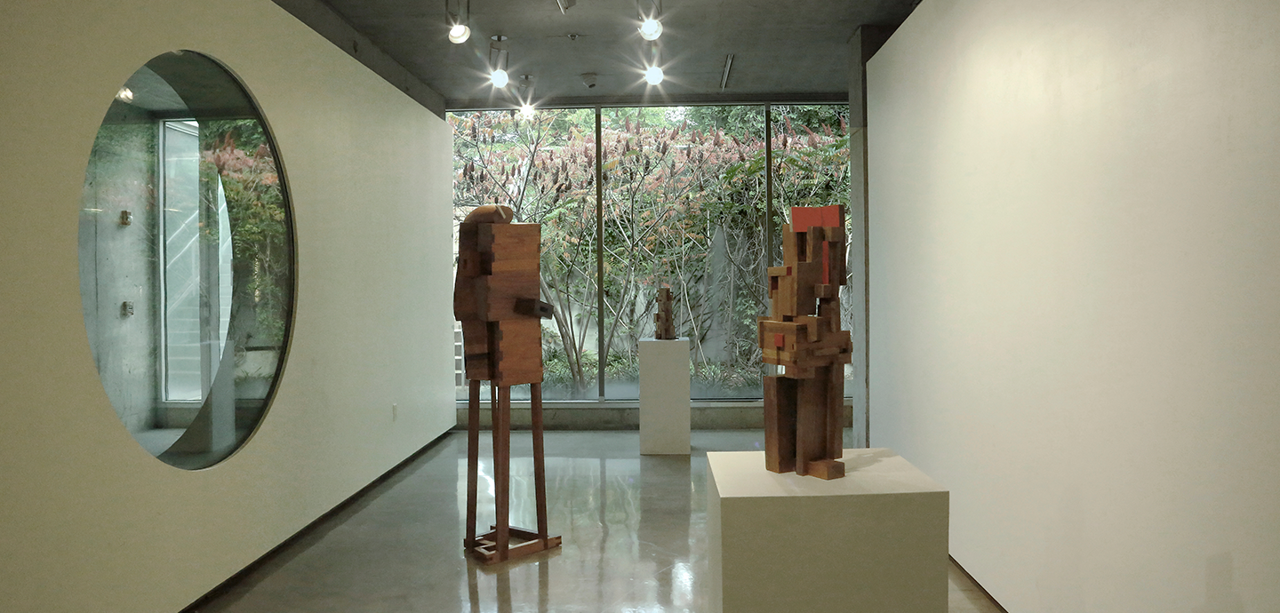 Abstract wooden sculpture piece with various sized rectangular pieces put together displayed on white pedestals.
