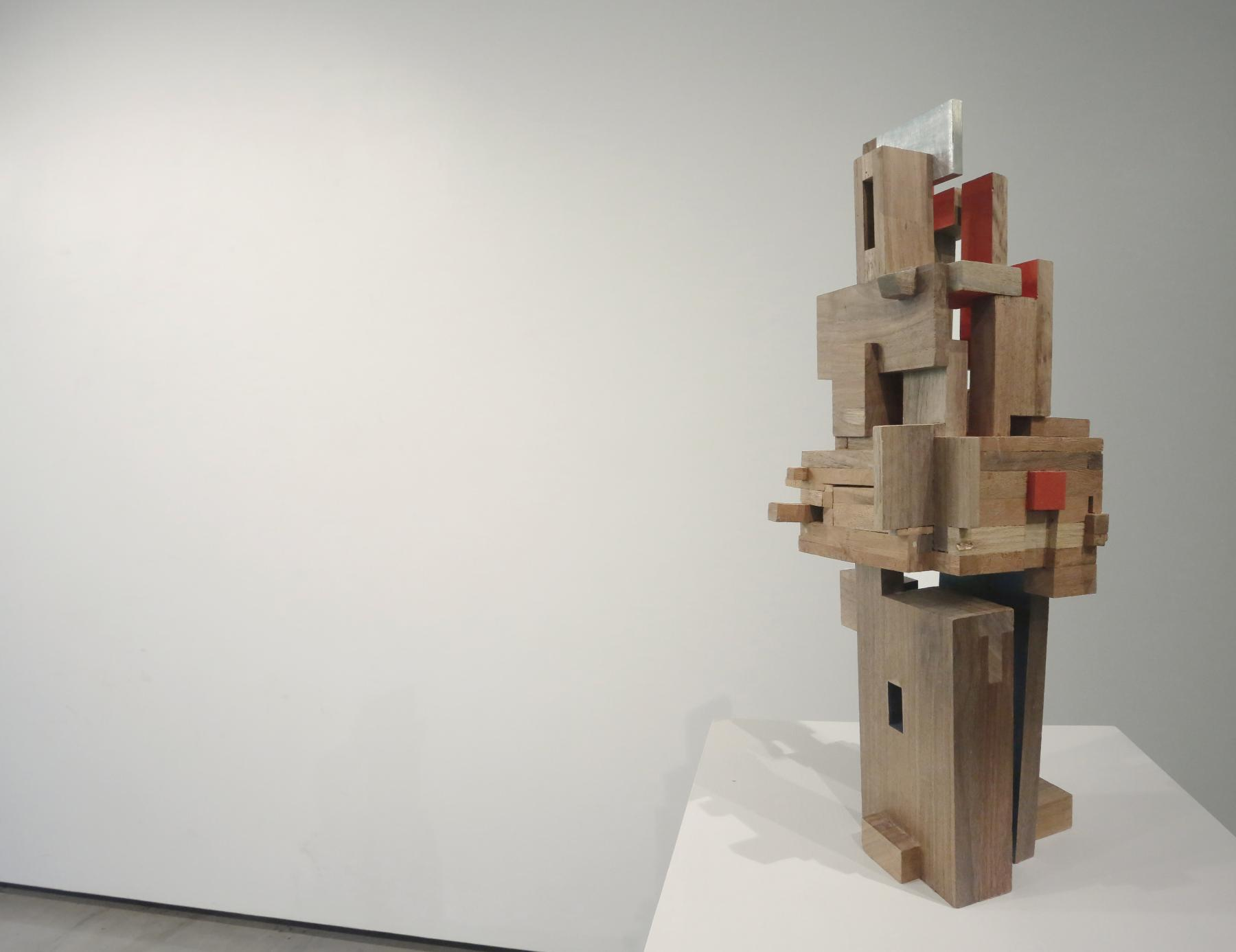 Abstract wooden sculpture piece with various sized rectangular pieces put together displayed on a white pedestal.
