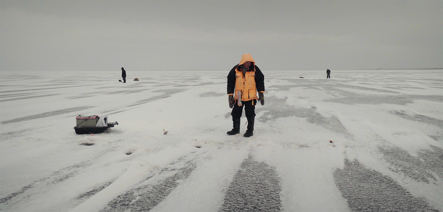 A man standing in a flat, desolate, and expansive snow covered environment.