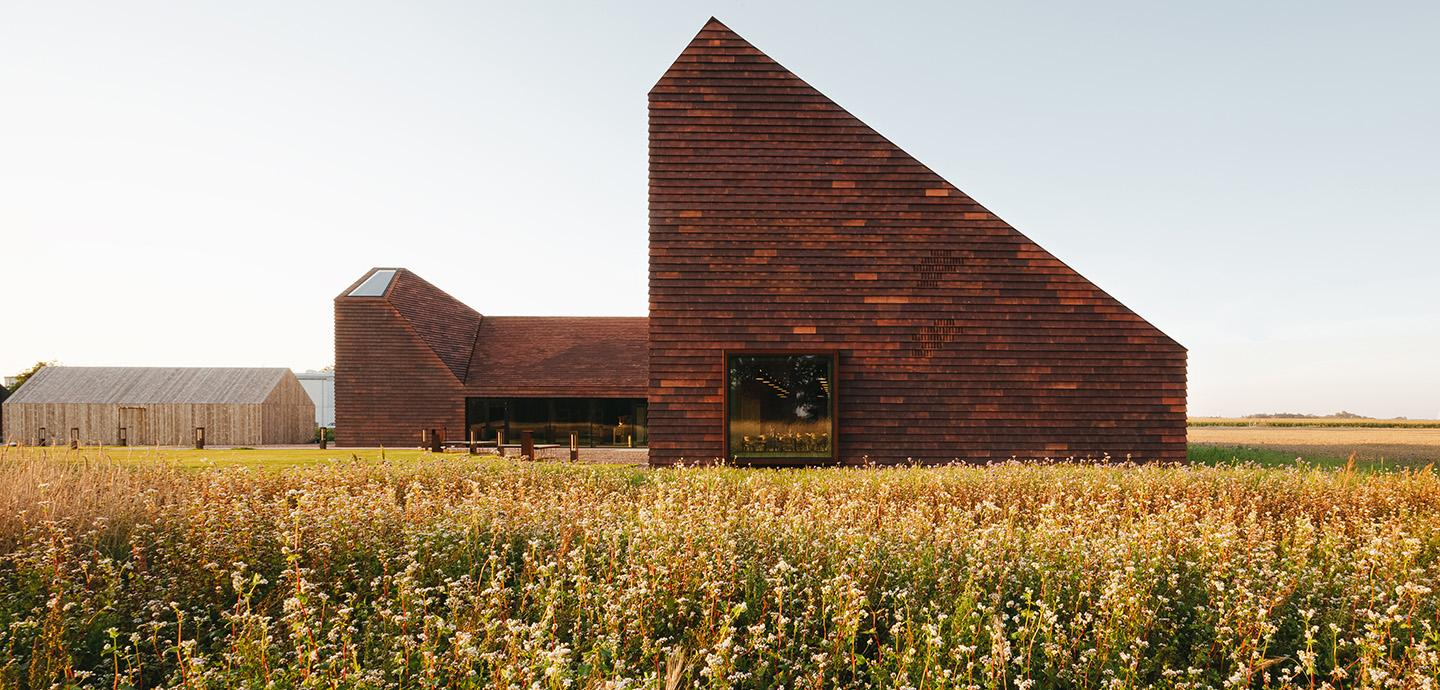 A modern brick structure situated in a field of golden and green toned plant life.