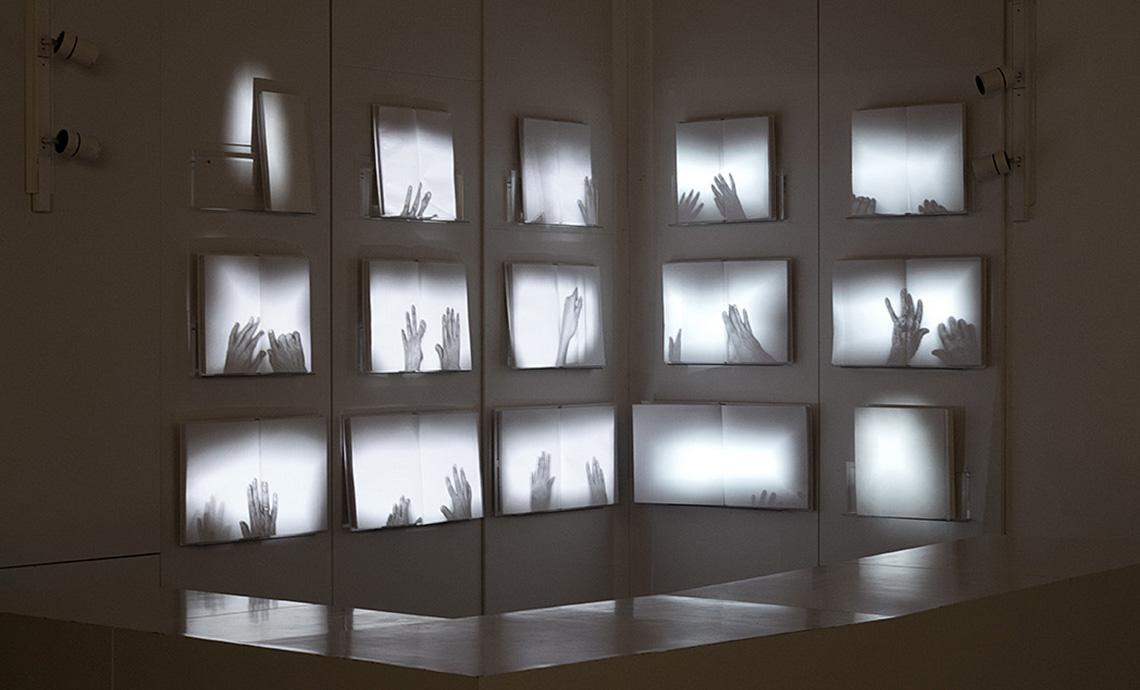 A modern gallery space with a series of video projections depicting the interior of blank hardcover books.