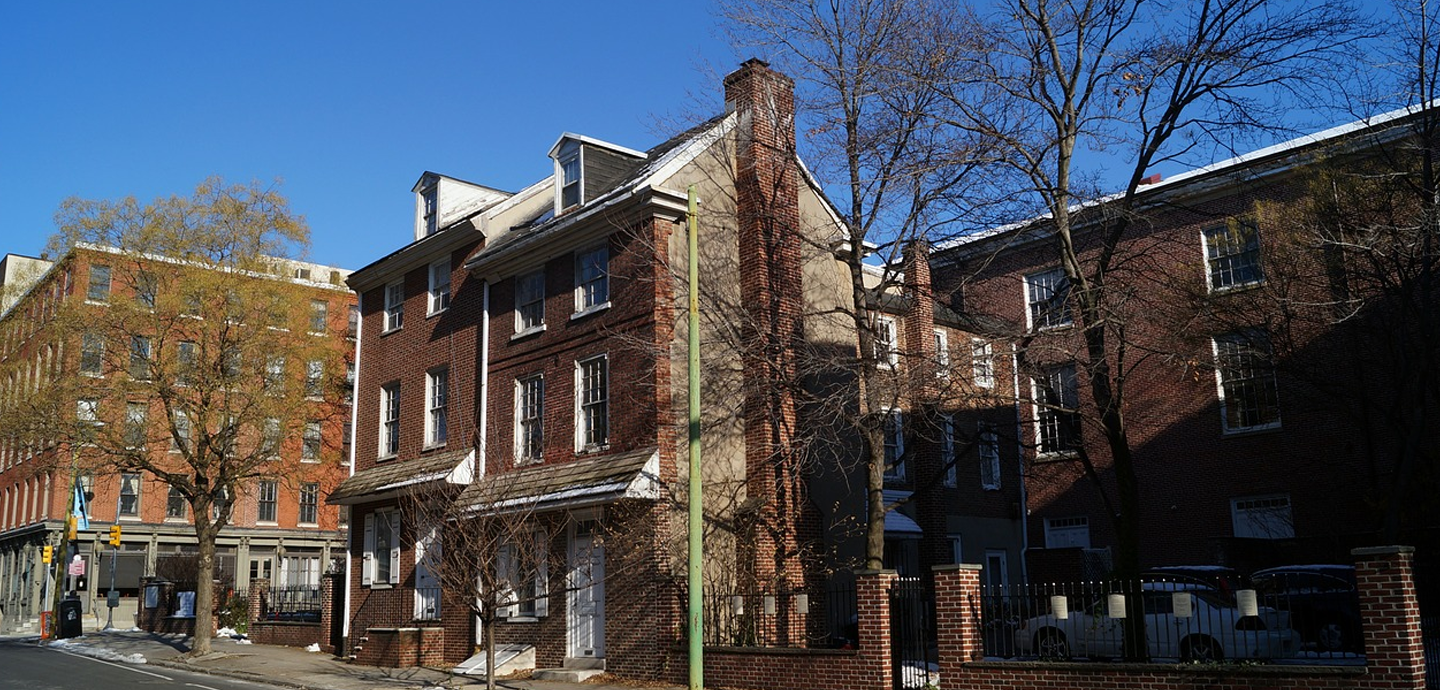 brick buildings with trees next to a green light post with a bright blue sky background.