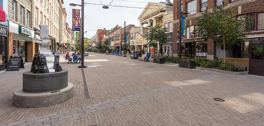 bricked pedestrian area flanked by retail buildings