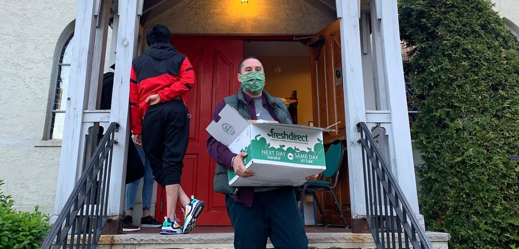 A man in a surgical mask on front steps holding a box