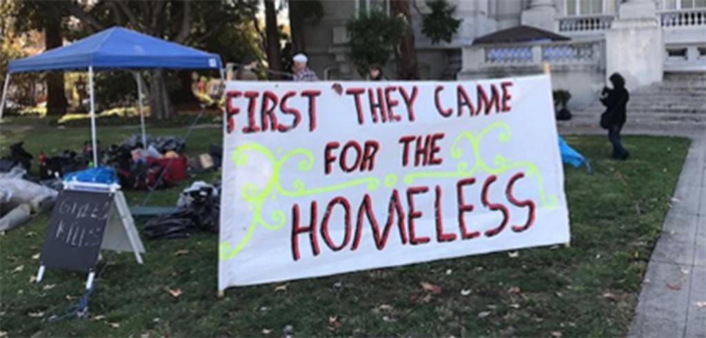 homeless camp on lawn of old city hall with large sign that reads First They Came for the Homeless