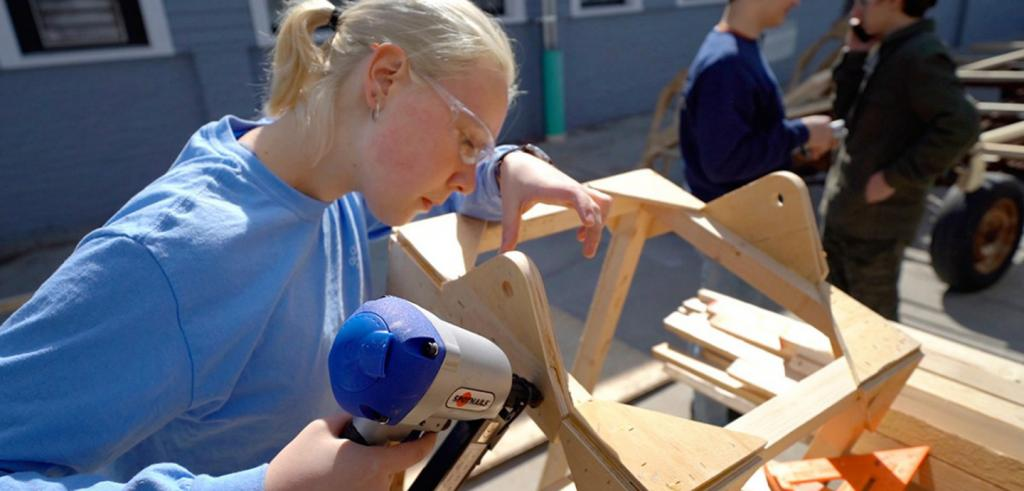 A young woman with blond hair uses a power tool to attach two piece of wood