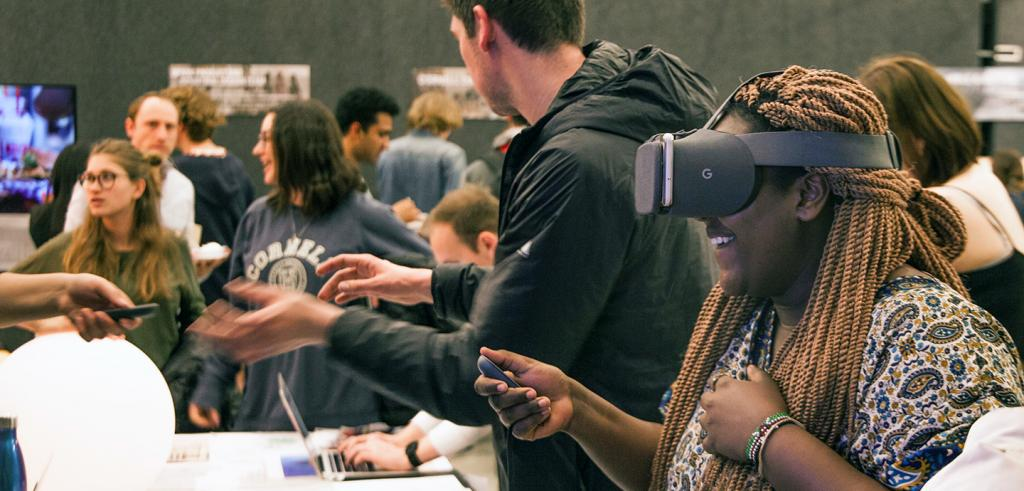 a woman with a VR headset and remote in a crown of people