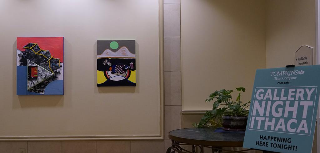 photograph of two paintings on a wall and a sign with text that reads gallery night ithaca