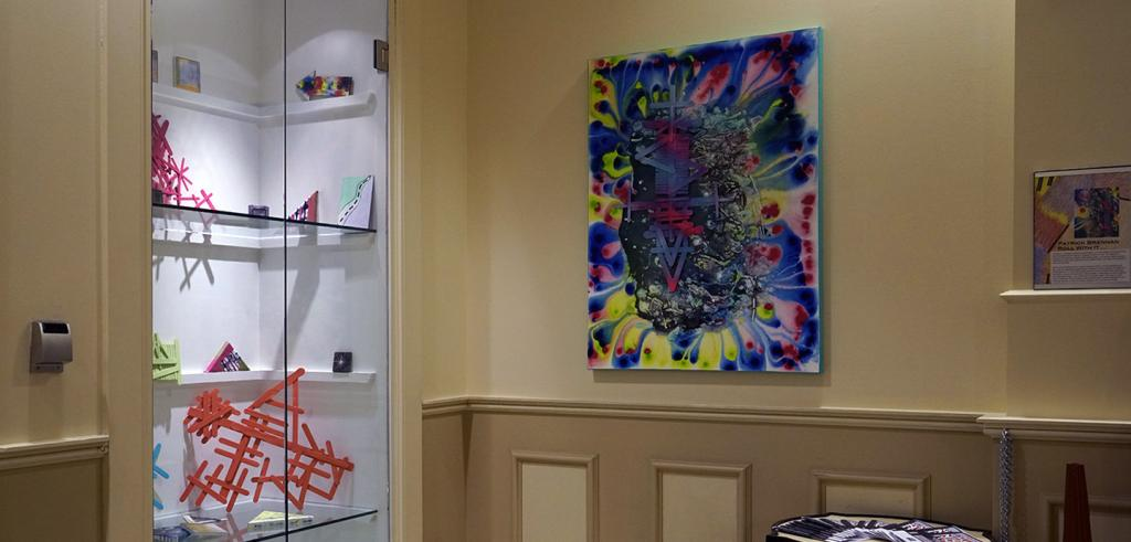 photograph of a colorful painting and art objects in a display case