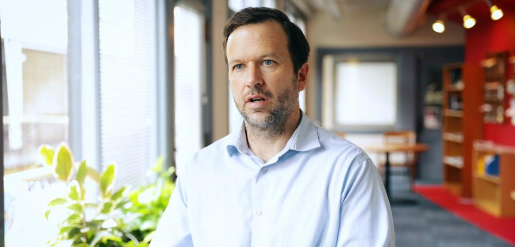 man with brown hair, short beard and blue eyes wearing a light blue button down shirt
