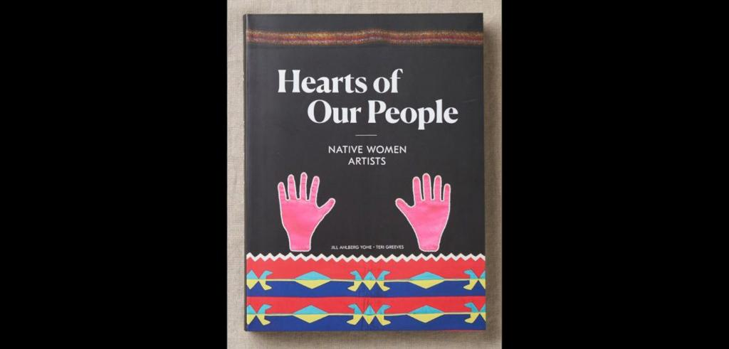 Book cover depicts two pink hands above a graphical pattern in red, blue, and yellow below a black background with the words