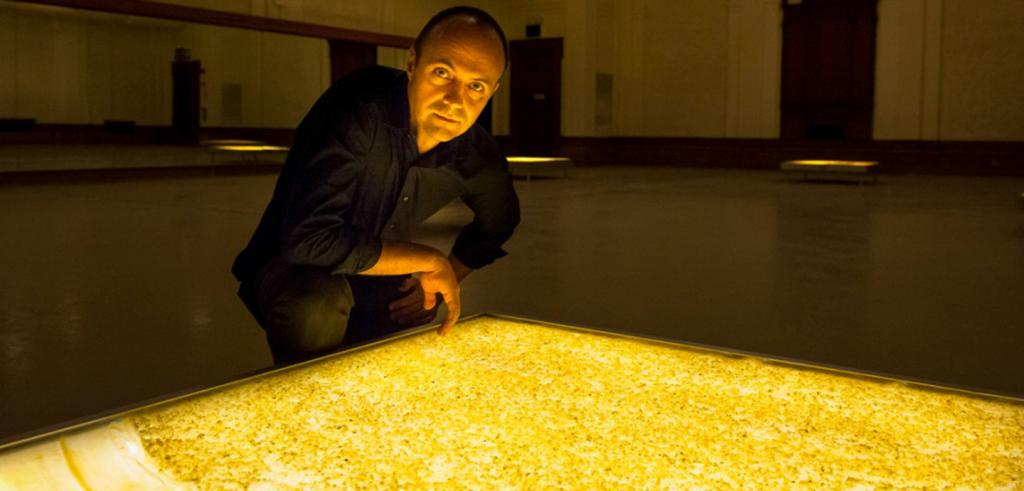 a man leans over a lit table surface in a large exhibition space