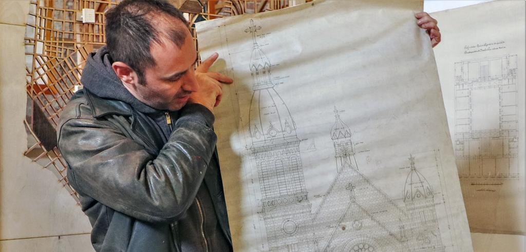 a man holding up an architectural sketch of a church