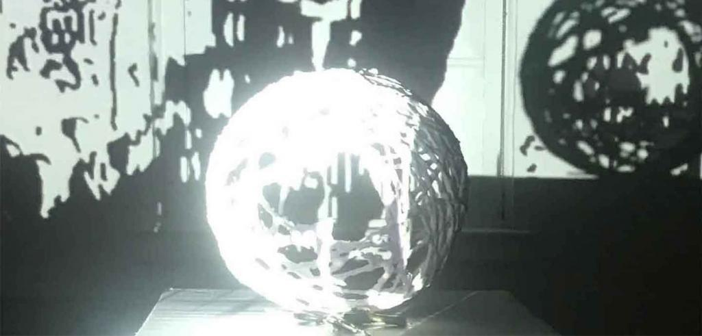 Black and white video still of a ball of yarn on a pedestal with shadows of a ball of yarn in the background.