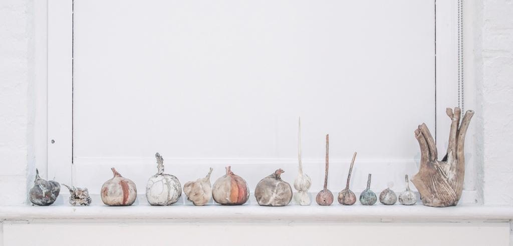 14 varying sculptures of turnips in white, orange and grey colors in a row on a white window sill