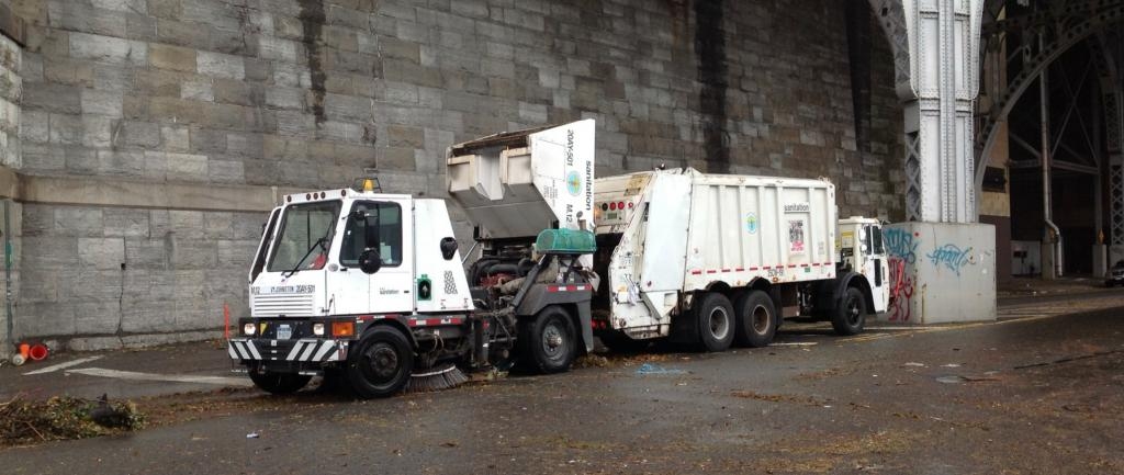 A white garbage truck in front of a concrete wall under an overpass.