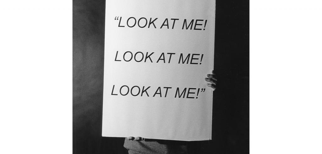 Black and white photograph of someone holding a sign stating Look at me! Look at me! Look at me!