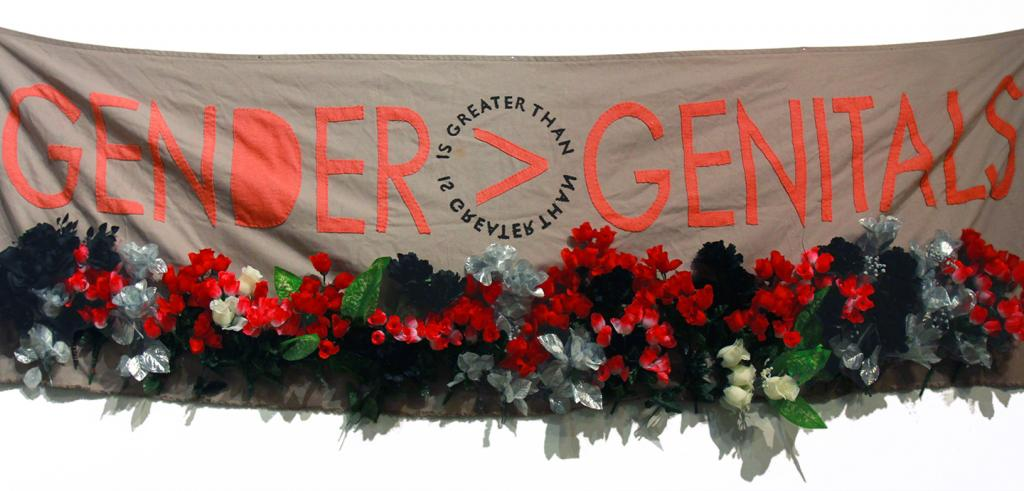 A fabric sign that reads 'gender is greater than genitals' sewn on a khaki colored banner with fake flowers attached beneath it.