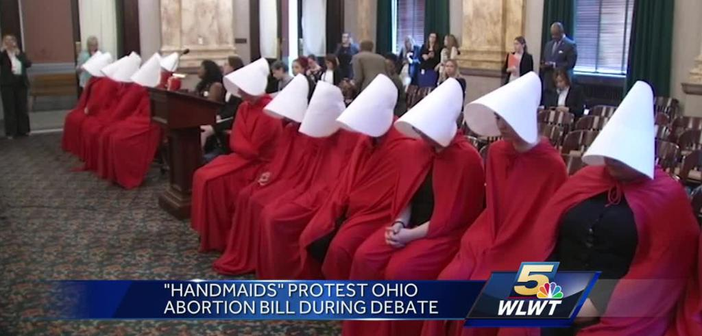 A row of women wearing red robes and white wimples protesting an abortion bill debate in a courtroom.