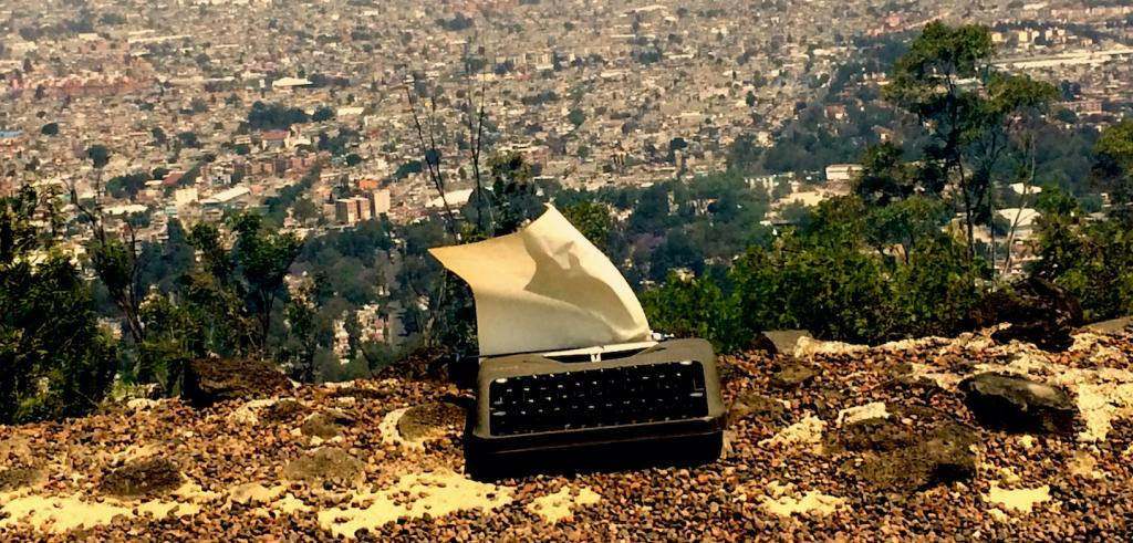 Typewriter on the ground with a blank piece of paper hanging from the top overlooking a city with trees in the distance.