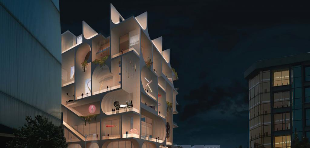 A night-time view of a six-story modern building whose glass sides are lit from within.