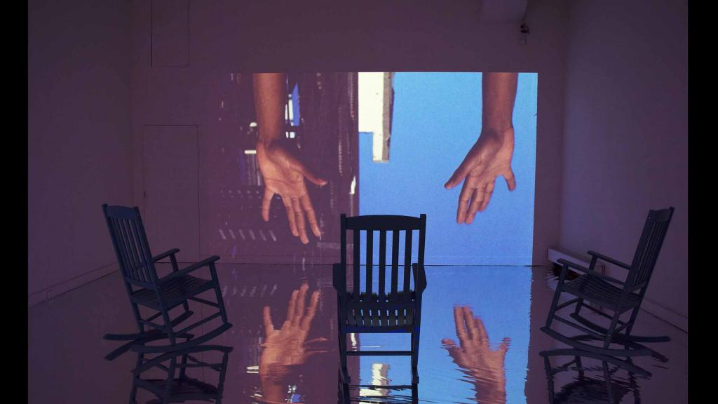 Empty room with three rocking chairs in front of a projection of two arms reaching down in front of a sky and building background.
