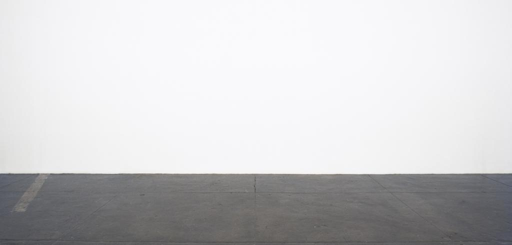 Blank white wall with a dark gray cement floor with a faded yellow line to the left.
