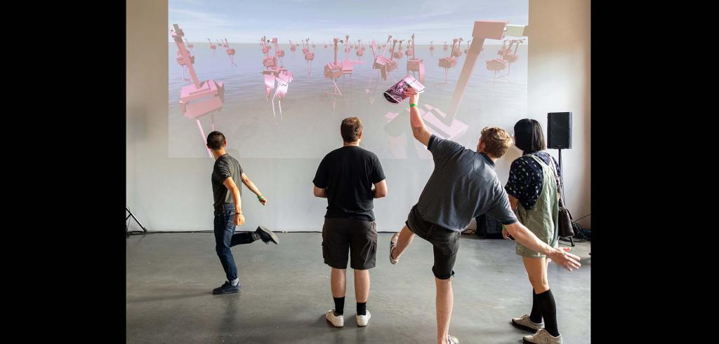 Four people looking at a projection of pink abstract flamingos with two people standing on one leg in front.